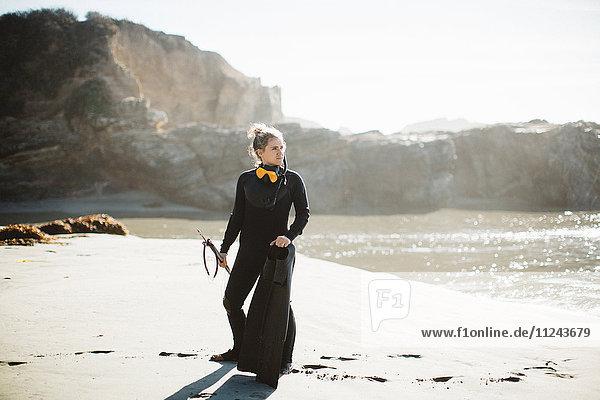 Diver with speargun on beach  Big Sur  California  USA
