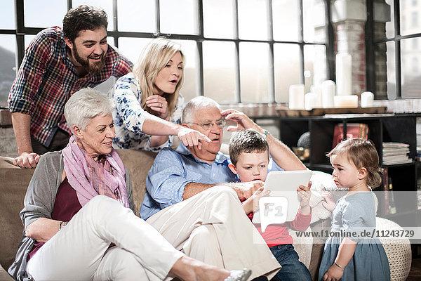 Drei-Generationen-Familie mit digitalem Tablett zu Hause