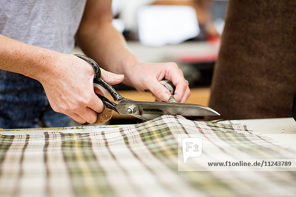 Woman cutting fabric in leather jacket manufacturers  close-up