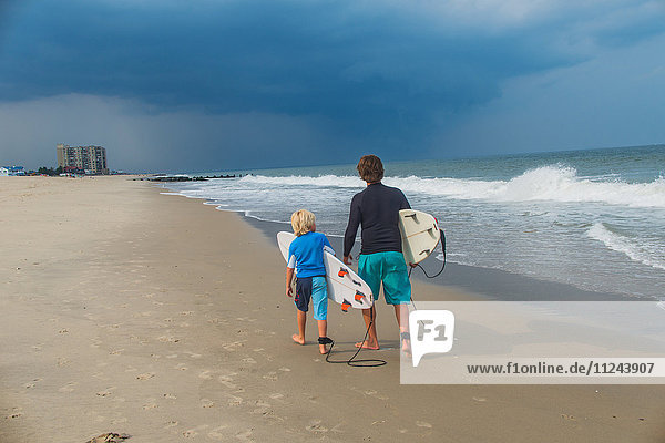 Father and son walking along beach  carrying surfboards  rear view