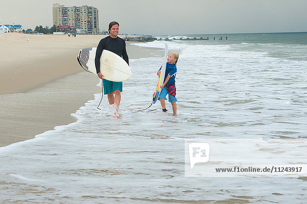 Father and son walking along beach  carrying surfboards