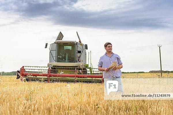 Landwirt mit einer Garbe Bio-Gerste auf dem Feld