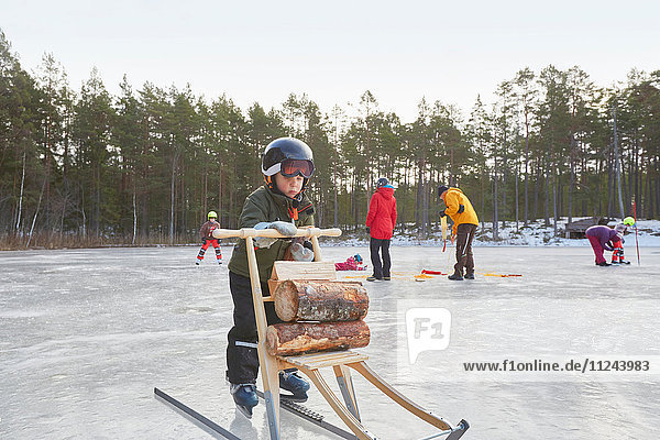 Junge lernt Schlittschuhlaufen mit Tritten auf gefrorenem See  Gavle  Schweden