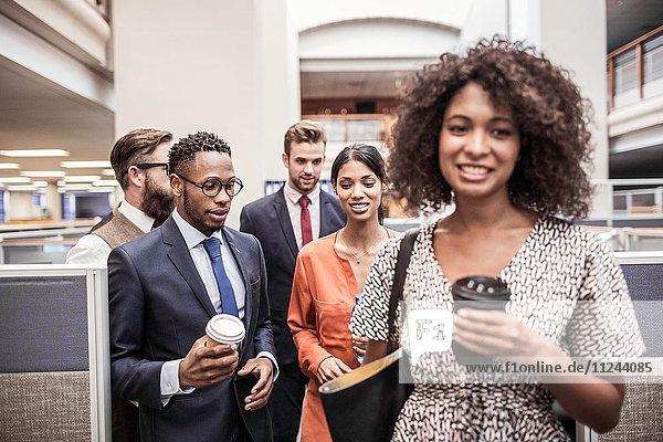 Geschäftsteam geht mit Kaffee zum Mitnehmen durchs Büro