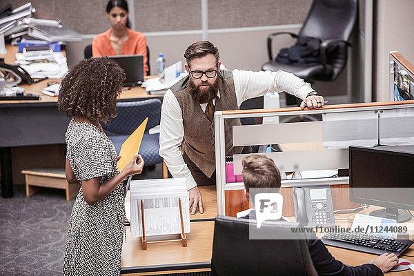 Geschäftsfrau und Männer unterhalten sich am Bürotisch