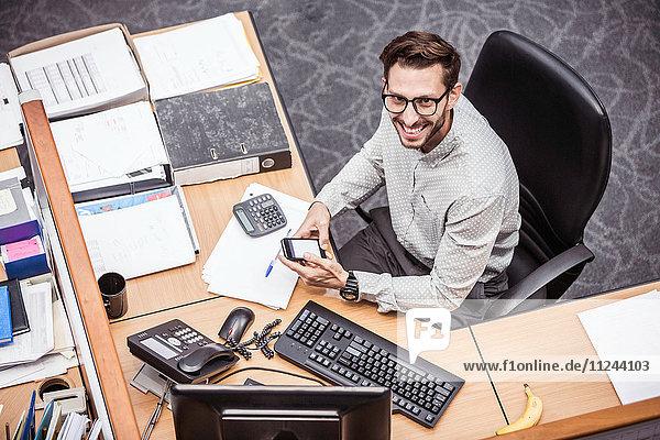 Draufsicht eines Geschäftsmannes  der ein Smartphone am Büroschreibtisch benutzt
