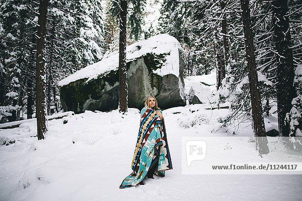 Frau in schneebedecktem Wald in Decke gehüllt