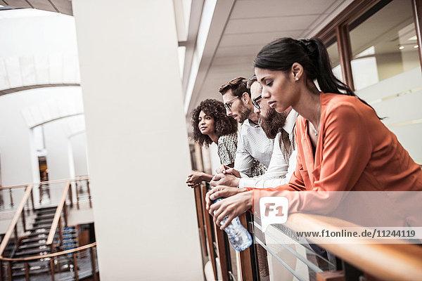 Geschäftsfrauen und -männer blicken vom Balkon des Büros