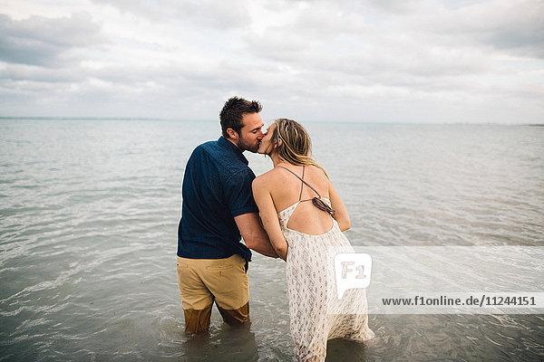 Rückansicht eines Paares  das knietief im Wasser küsst
