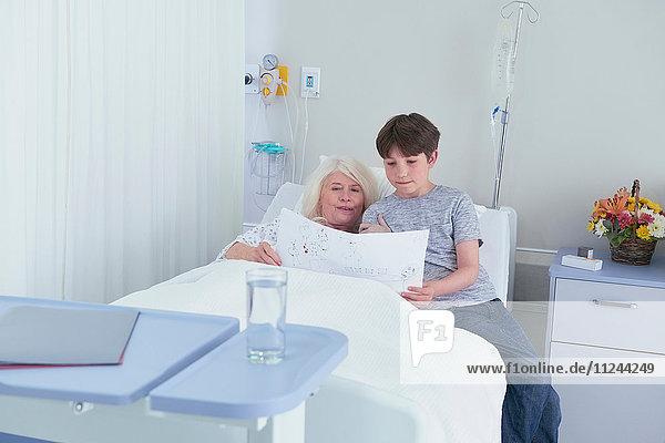 Ältere Patientin im Krankenhausbett mit Blick auf die Zeichnung ihres Enkels