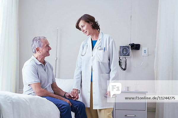 Ärztinnen erklären einem älteren männlichen Patienten im Krankenhausbett
