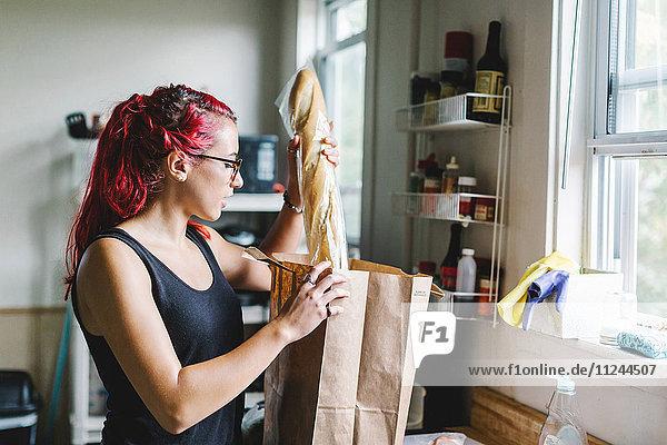 Junge Frau mit rosa Haaren packt Baguette aus Einkaufstasche in der Küche aus