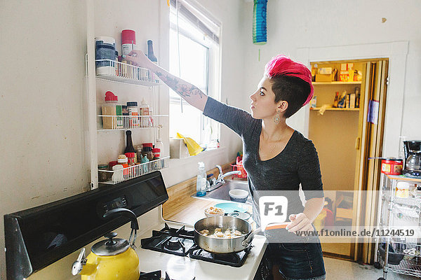 Young woman with pink hair preparing food on kitchen hob