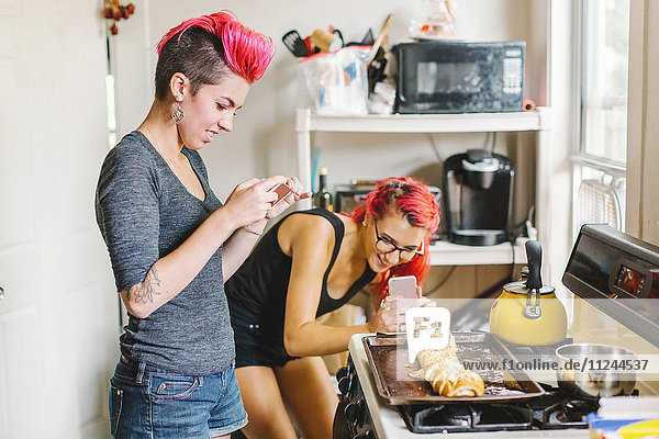 Two young women with pink hair taking smartphone photographs of stuffed baguette in kitchen