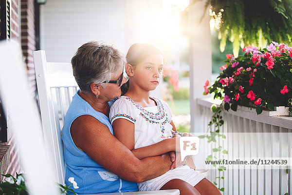 Girl sitting on grandmother's lap in porch at sunset