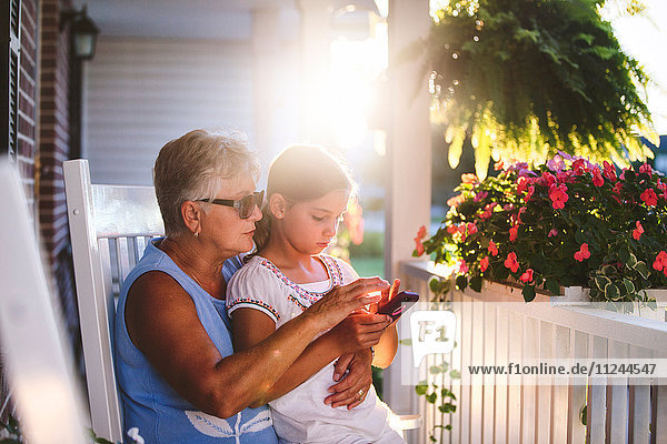 Girl and grandmother playing smartphone game on porch at sunset