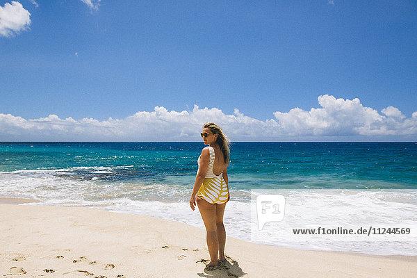 Schwangere Frau mittleren Alters im Badeanzug beim Rückblick vom Strand von Makua  Hawaii  USA