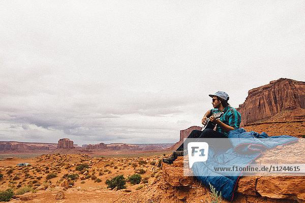 Auf Rock sitzender junger Mann spielt Akustikgitarre  Monument Valley  Arizona  USA