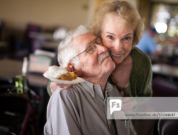 Ältere Frau umarmt älteren Mann und lächelt