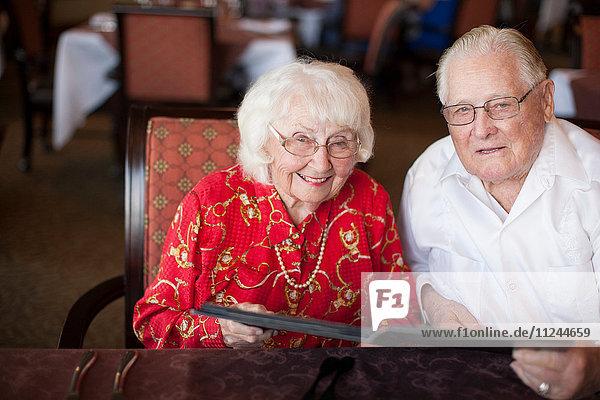 Porträt eines älteren Ehepaares  das lächelnd am Tisch im Restaurant sitzt
