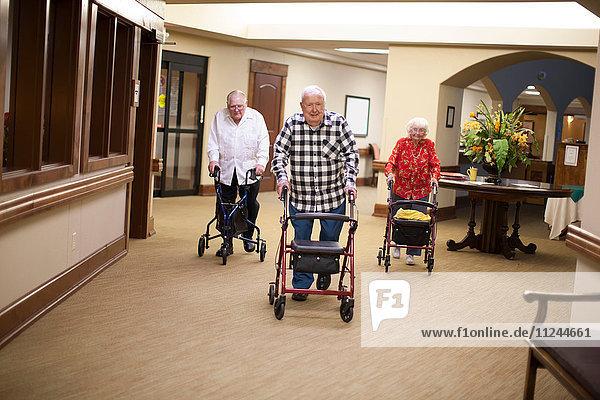 Drei ältere Erwachsene  die mit Gehhilfen im Haus gehen