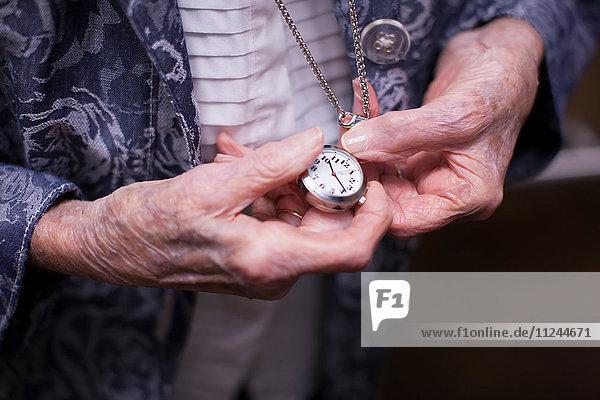 Ältere Frau  Taschenuhr haltend  Mittelteil  Nahaufnahme