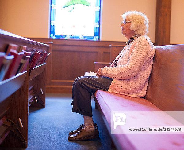 Ältere Frau sitzt in der Kapelle