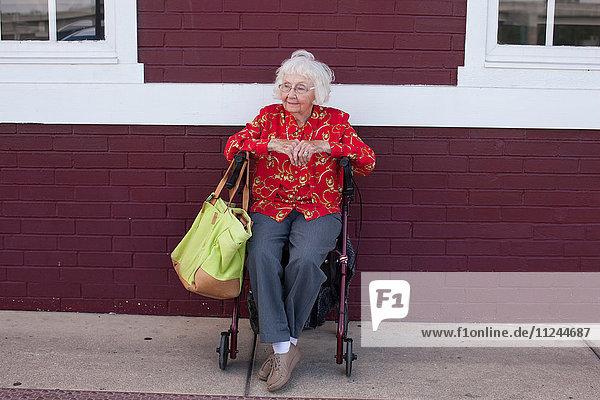 Ältere Frau im Rollstuhl sitzend  im Freien