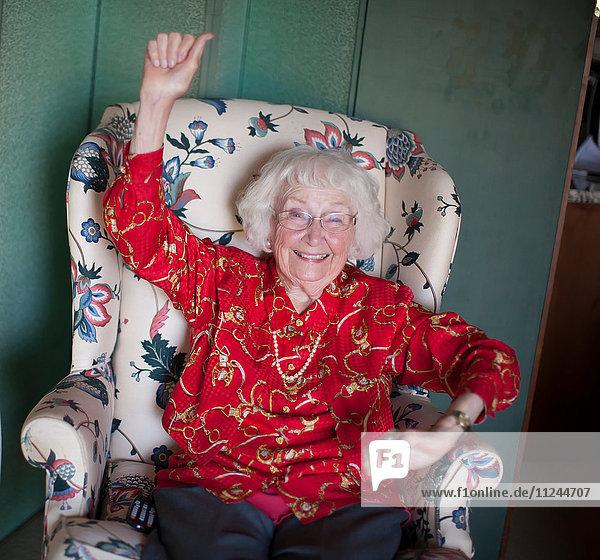 Porträt einer älteren Frau auf einem Stuhl sitzend  lächelnd  den Arm erhoben
