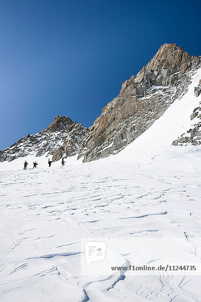 Four male snowboarders hiking up snow-covered landscape  Trient  Swiss Alps  Switzerland