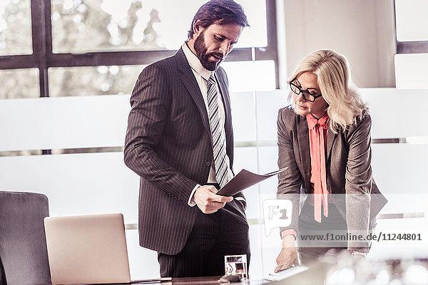Geschäftsfrau und Geschäftsmann lesen Papierkram im Büro