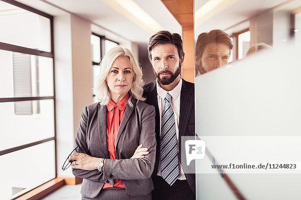 Porträt einer Geschäftsfrau und eines Geschäftsmannes an einer Bürotür