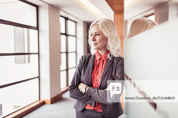 Porträt einer reifen Geschäftsfrau mit verschränkten Armen am Eingang zum Büro