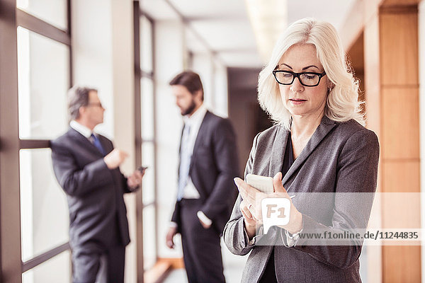 Geschäftsfrau liest Smartphone-Update im Bürokorridor