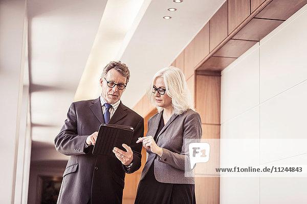 Geschäftsfrau und Mann benutzen digitales Tablet im Bürokorridor