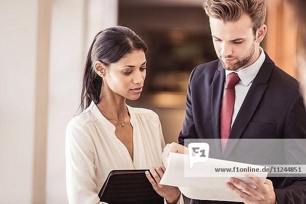 Junger Geschäftsmann und junge Geschäftsfrau lesen Papierkram im Büro