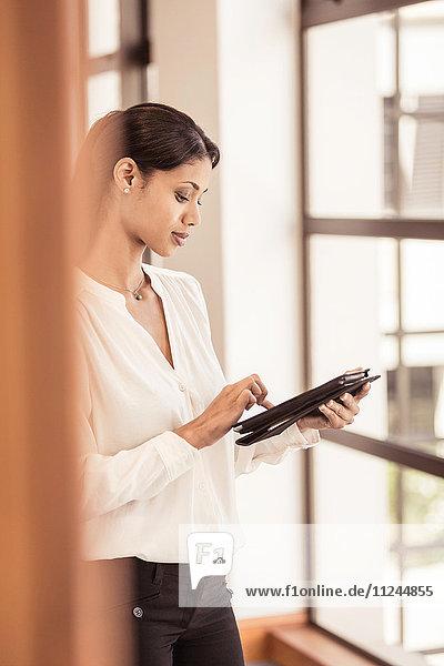 Junge Geschäftsfrau benutzt digitales Tablet im Büro