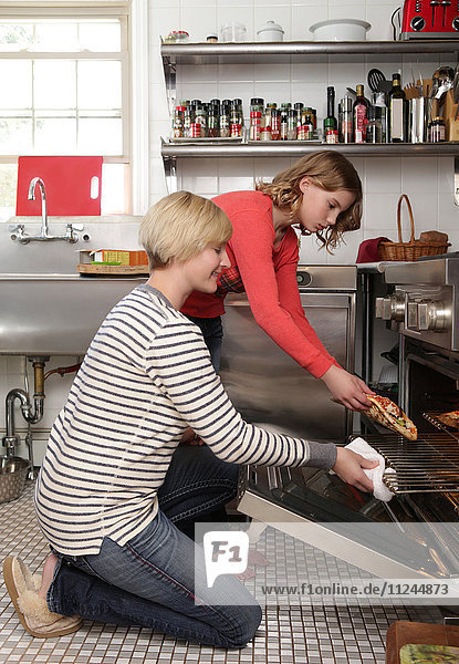 Mother and daughter in kitchen  placing pizza in oven