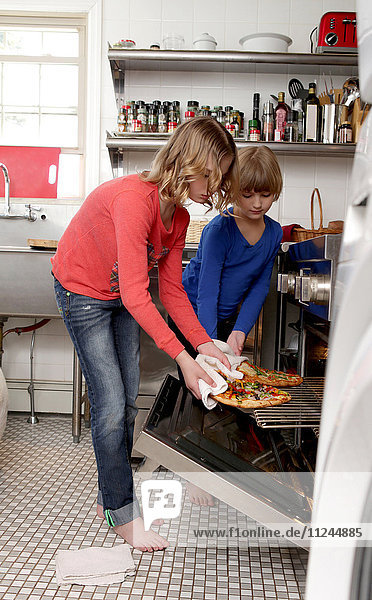 Two young girls in kitchen  taking pizza from oven