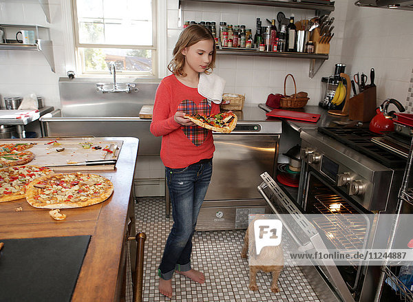 Young girl in kitchen  putting pizza in oven