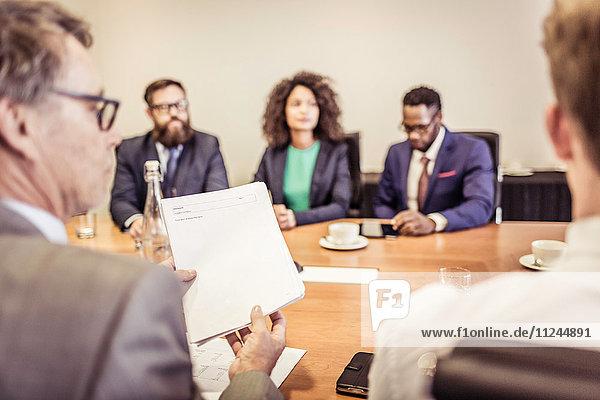 Blick über die Schulter von Geschäftsfrauen und -männern bei Konferenztischgesprächen