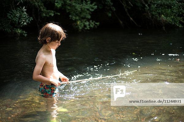 Boy waist deep in water holding stick