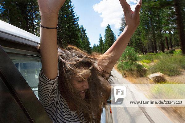 Junge Frau  die sich aus einem fahrenden Autofenster lehnt  Mammoth Lakes  Kalifornien  USA
