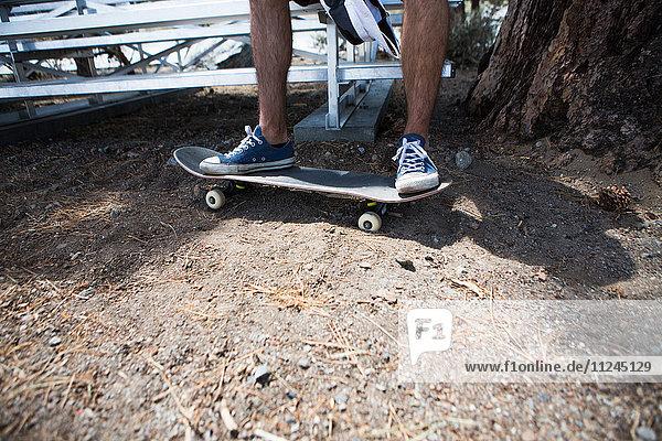 Beine und Füsse eines männlichen Skateboardfahrers am Stadionsitz