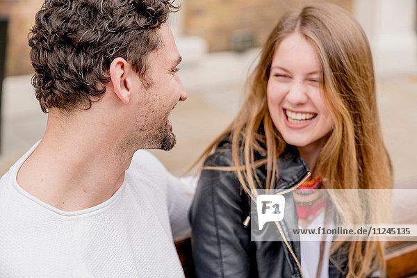 Glückliches junges Paar auf Parkbank sitzend