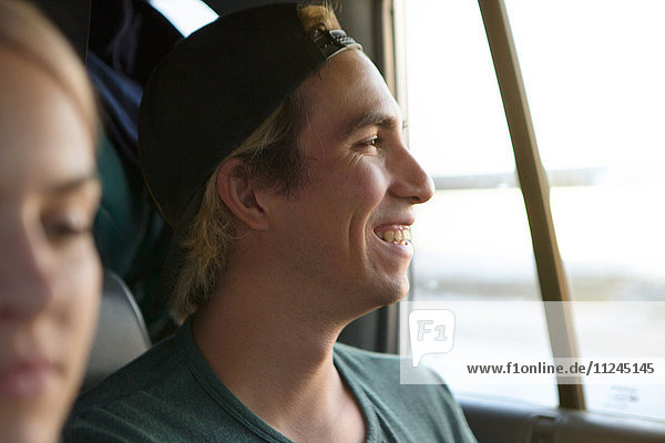 Happy young man looking out through car window