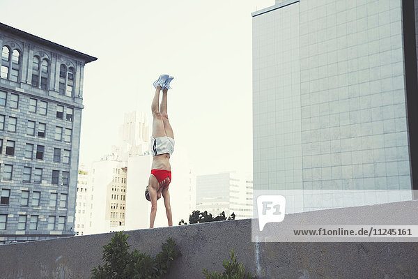 Junge Frau macht Handstand an der Wand im Freien