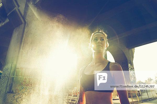 Porträt einer jungen Frau in städtischer Umgebung  die eine Sportweste trägt
