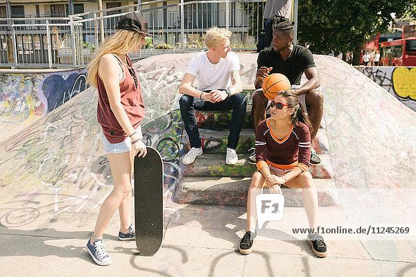 Vier männliche und weibliche Basketball- und Skateboardfreunde sitzen im städtischen Skatepark und unterhalten sich