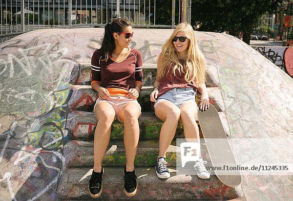 Two female skateboarding friends chatting in skatepark